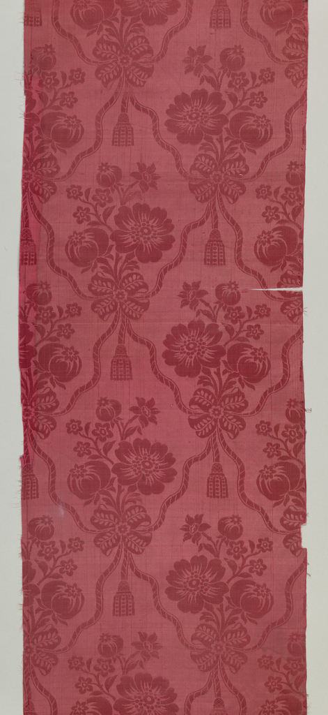 Panel of red silk damask with a pattern of ribbon festoons and clusters of flowers.