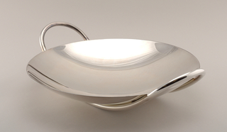 Concave round bowl with rounded base. Tubular metal handles in continuous loop forming base and extending above lip to create open oval handles.