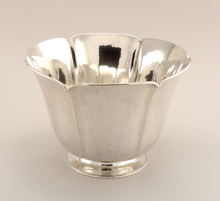 Tall, tapering six-sided bowl with everted lobed rim and circular foot; hammered surface and applied border.