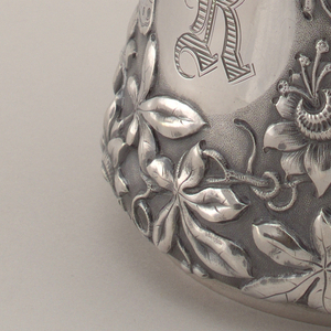 """Conical shape, slightly flaring rim, and angular handle terminating in leaf scroll.  Whole body, except for circular cartouche with engraved """"R"""", covered with repousse and chased flowers, leaves and butterflies on granular ground."""