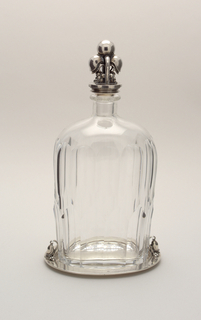 A bottle shaped decanter with a silver stand and stopper. Both stopper and stand have details of leave like forms.