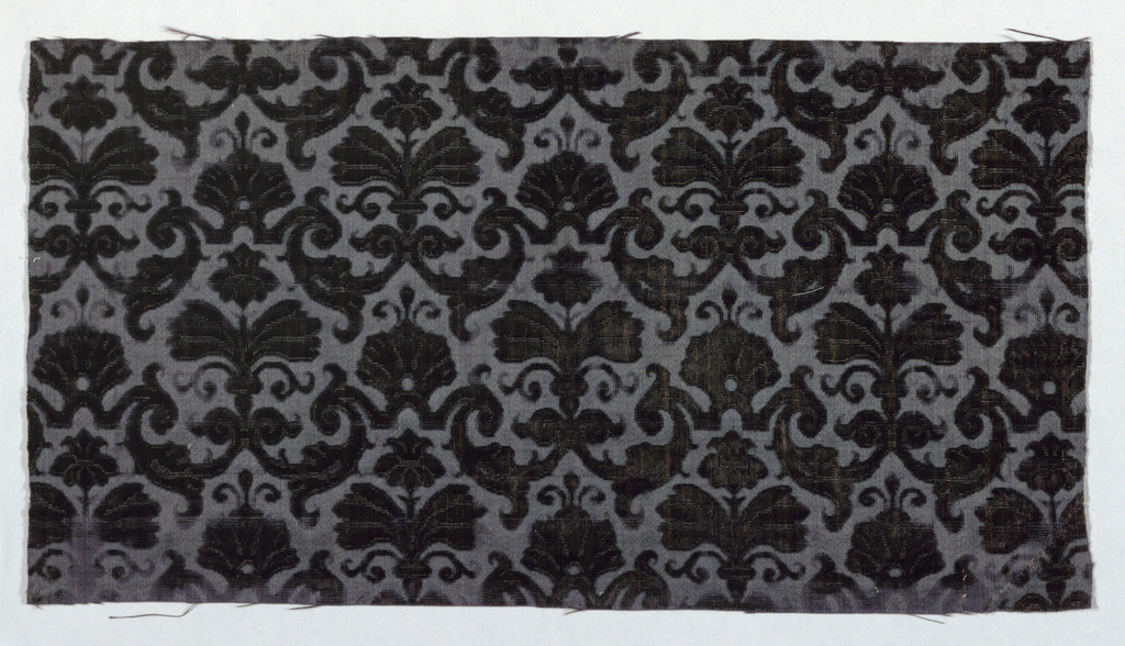 Fragment of dark blue cut and uncut velvet in a small-scale symmetrical pattern of plants and foliage.