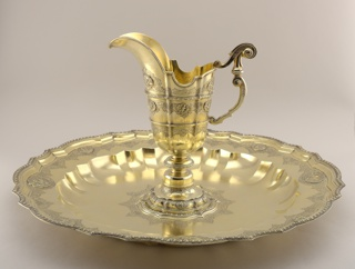 Helmet-shaped ewer on domed foot, engraved with strapwork, and bearing lobed medallions in two sizes, the larger representing Asia and America, the smaller Geometry, Music, etc.  Double-scrolled handle. The basin is marli alternately lobed and straight, with guilloche band, strapwork engraving, and four large relief medallions representing the Four Elements, and four smaller medallions of the Four Continents.  Gadrooned well; raised center with relief medallion of Hercules crowned by Victory, framed in guilloche border and strapwork.