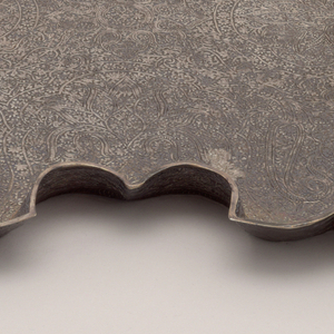 Four-lobed square form composed of flat base with slightly out-curved, raised scalloped rim; floor of tray and inner and outer rim decorated overall with conventionalized hammered floral motives.