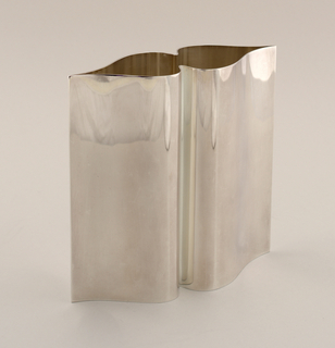 Straight-sided oblong vase with front and back sides with double curves, soldered in straight line at outer edges of curves to form sharp upright ribs.  Flat polished surface, flat base following shape of sides.