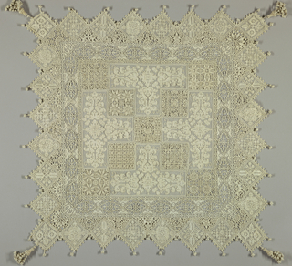 Scrolling floral motifs are contained within four T shapes which face inward. Squares of bobbin lace in imitation of reticello complete the field. The border with floral motifs set in diamonds has a knotted tassel at each point, four elaborate tassels at corners.
