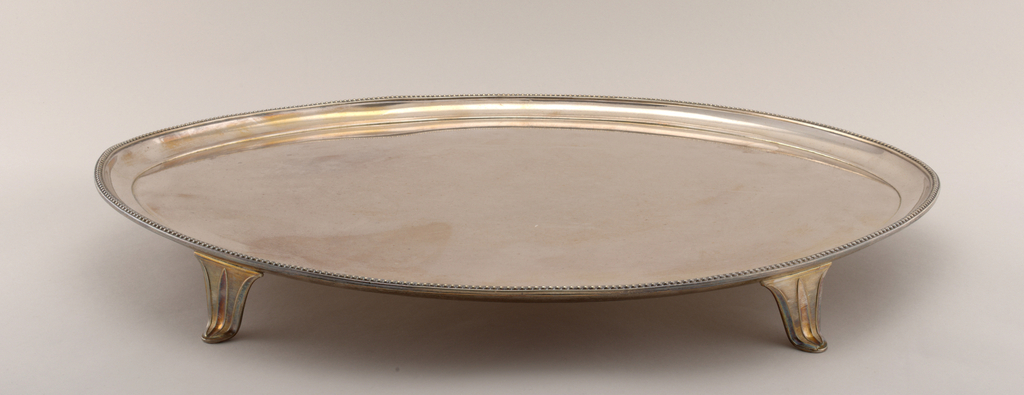 Oval, with applied up-curved rim, beaded at edge; four strap feet each stamped with losenge motif; underside of tray tinned.