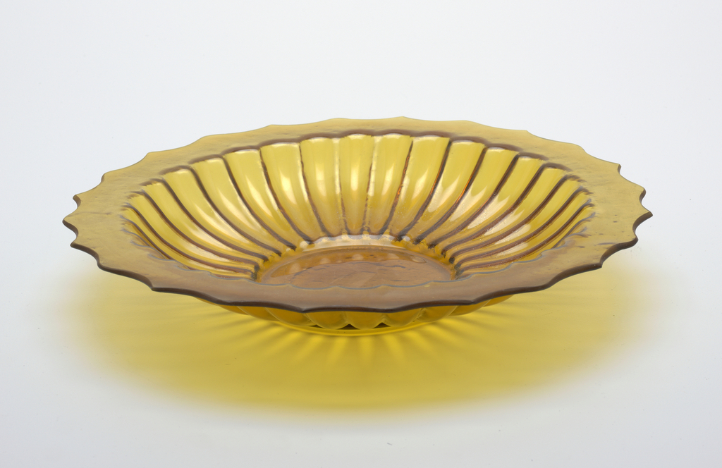 Wide shallow circular bowl with molded lobed sides and flat shaped rim; amber-colored glass; smooth inside, textured outside.
