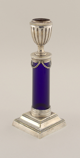 Two-tiered square base with two rows of beading, of silver. Blue glass column shaft, capped by silver capital hung with three bead swags. Candleholder  in the shape of a fluted urn, silver. No marks.