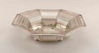 Octagonal basket with flaring sides pierced in bands of lancets and circles. Four ball feet.