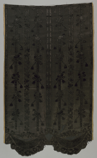 Skirt panel of black figured velvet with narrow vertical stripes of varying types including ribbon-and-leaf serpentine, cardinal's hats, tassels, and flowers on a stripe, and a sawtooth stripe with a diamond center. Bottom edge has two wide scallops comprised of swags and flower heads held aloft by ribbons.