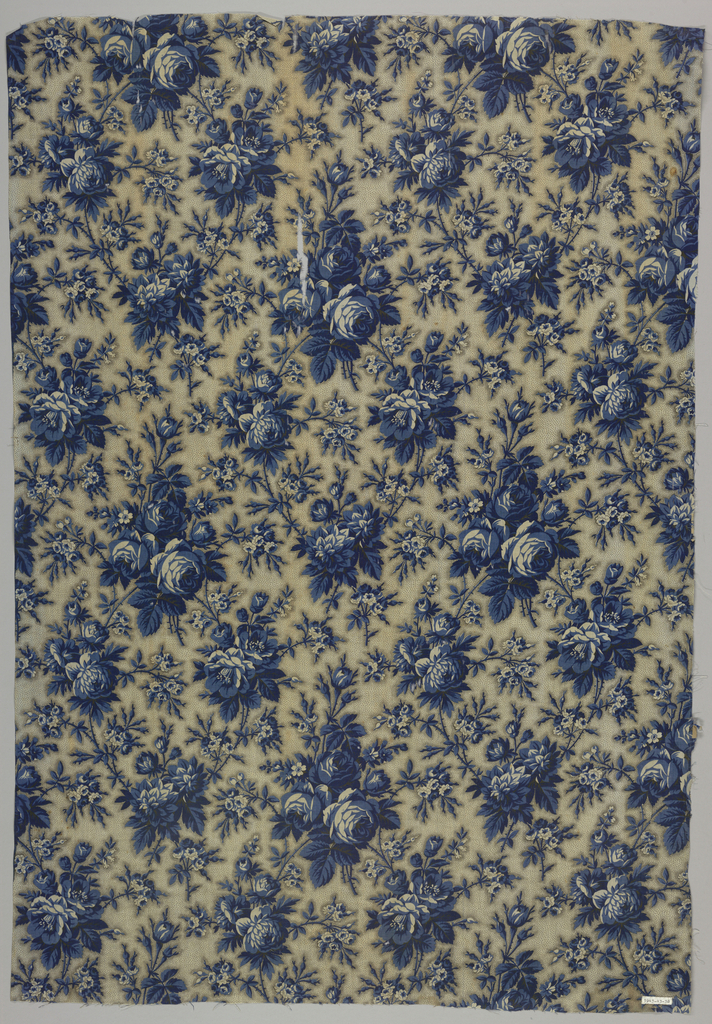 All-over repeat of large scale flowers in blue and background of blue picotage dots. One selvage present.
