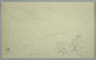 Horizontal oblique view into a valley with bushes and trees standing on a slope in the right foreground and with two peaks rising from the mountain range in the background.