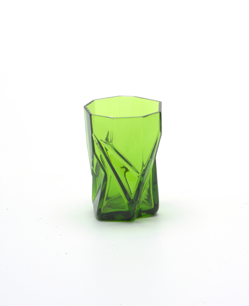 Irregularly shaped transparent green body, the uneven surface appearing as a series of faceted planes and angles.