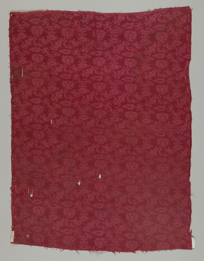 Red damask in an allover repeating pattern of a bar with a scrolling floral forms arranged in rows.