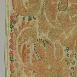 Elaborate scrolls in pink with touches of green and white. Both selvages present.