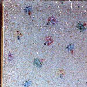 Small stylized floral motif printed on speckled ground.  The flowers are printed in colors and are turned in different directions.