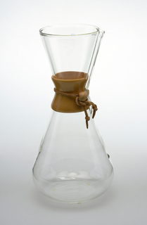 Hourglass-shaped coffee maker of transparent glass with high neck and circular mouth molded with a narrow spout; tapered wood collar/hand grip at neck tied with leather thong with bead stop; small projecting dot as water level indicator in lower body, vertically aligned with spout.