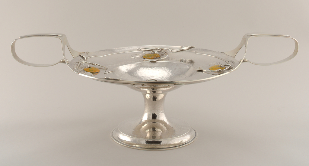 """Circular raised foot with stepped platform, tapered to trumpet stem.  Broad bowl with heavily textured """"hammered"""" surface, deeply concave and with broad upturned rim.  Rim applied both sides with wire vines, leaves, and a green/orange gourd, enamel on silver.  At each side a broad strap emerges from two straps at edge of bowl to form handles attached to bowl edge.  Applied small buttons at lower part of each handle."""