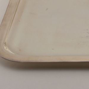 Rectangular silver-plated tray.  Part of a six piece tea service.  The tea service relies on pure geometric form and highly reflective surfaces for its effect.