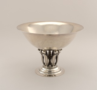 A raised silver bowl with a wide rim. The raised foot holds the bowl up with curled leaf-like legs and a beaded center.