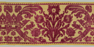 Large-scale symmetrical repeat of crown clasping two out-curving lobed leaves alternating or framing spreading bouquet of tulips flanked by small birds. In crimson cut and uncut velvet on gold ground now sparsely covered with tarnished silver. Lobed guard strip top and bottom. Two broad selvages striped in pink.