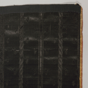 """Skirt fragment in all black with a pattern in cut and uncut pile. Narrow decorated vertical stripes on ground scattered with tiny sprigs. Deep hem decoration of symmetrical scenes of fishing figures on either side of a stream swirling under a double-arched bridge alternating with dueling figures in front of allée of obelisks. Portico topped by coronet and with unidentified initials """"LL"""" in background. Wide pink and yellow striped satin selvages."""