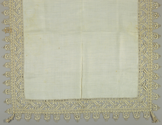 Linen plain weave table cover with a needle lace border. An acorn pattern on the diagonal fits into squares. Acorn changes direction in each square. Deeply scalloped border with a knotted tassel in each corner.