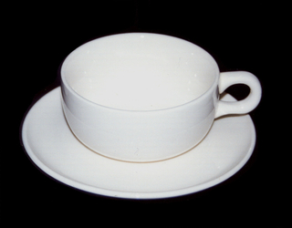 Glazed white cup and saucer. Wide-mouthed cup with C-shaped handle.