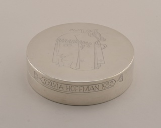 "Circular form, lid engraved with stylized, veiled ancient Greek female head in profile.  Side of lid engraved in banner-like cartouche: ""Sylvia Hoffman 1938"". (Set with 1998-21-1,2)"