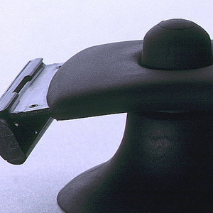 Wide, curved, black, rubber handle, with hole near top and blade element at end; razor snaps on to back of black suction cup accessory through hole.