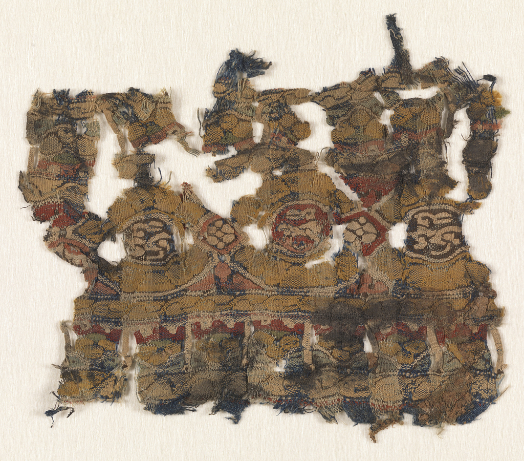 Small fragmentary tapestry band with interlaced ovals containing a central motif, perhaps a running hare. Guard borders above and below.