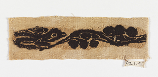 Fragment of narrow decorative band mounted on modern plain weave linen. Pattern in purple on white ground. Lizard (?) head.