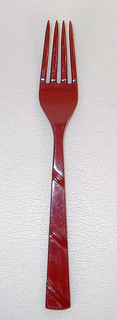 Red fork with three diagonal stripes on handle, part of a set.