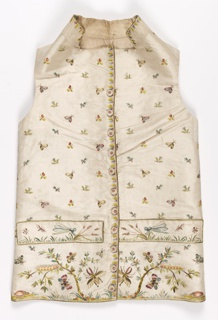Gentleman's embroidered waistcoat with standing collar, straight hem, pocket welts and covered buttons. Embroidered in multicolored silks in more than twenty colors. Over-all spot pattern of flowers and butterflies on the top half. Leafy branches, flowers and insects such as beetles, caterpillars, butterflies, and dragonflies are on the bottom half.