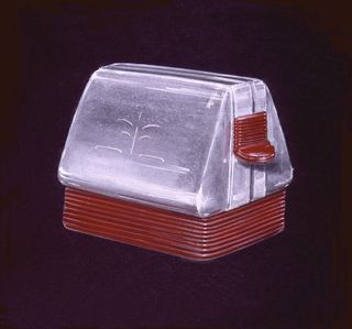 Three-quarter view of a streamlined toaster in chrome with wine colored horizontally grooved base and matching plastic knob.