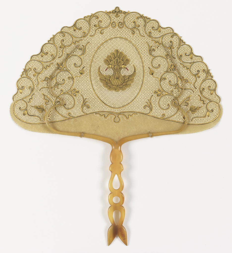 Handscreen in a semi-circular form. Pierced parchment leaf with an oval center medallion with a gilded two-headed bird with red beaks and feathers outlined in black, surrounded by gilt scroll decoration. Handle of pierced horn with slender curved horn holders stitched to parchment with tan cotton thread.