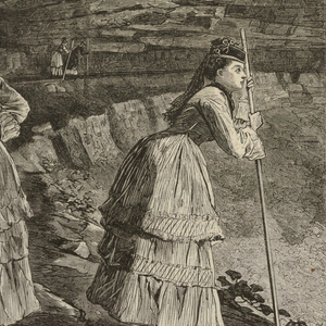 Two women with mountain climbing sticks looking at the falls.  In the mid center a man and woman climb the hill and in the background smaller groups of people can be seen along the edge of cliff under the falls.