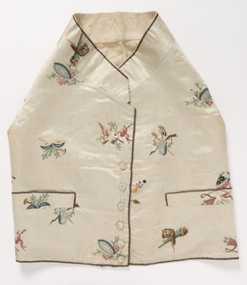Child's short waistcoat with high standing collar, embroidered with scattered patriotic motifs including shields, crests, and drums with crossed flags, in many colors on white.