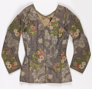 Woman's bodice in pale lavender silk brocaded with rococo meanders filled with lace-like diaper patterns, and sprays of naturalistic flowers in greens, pinks, and ivory. Watteau-style pleated back.