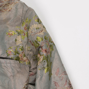 Woman's bodice with long sleeves, rounded square neckline, pointed front. Gray silk brocaded with sprays of naturalistic flowers in pastel shades.