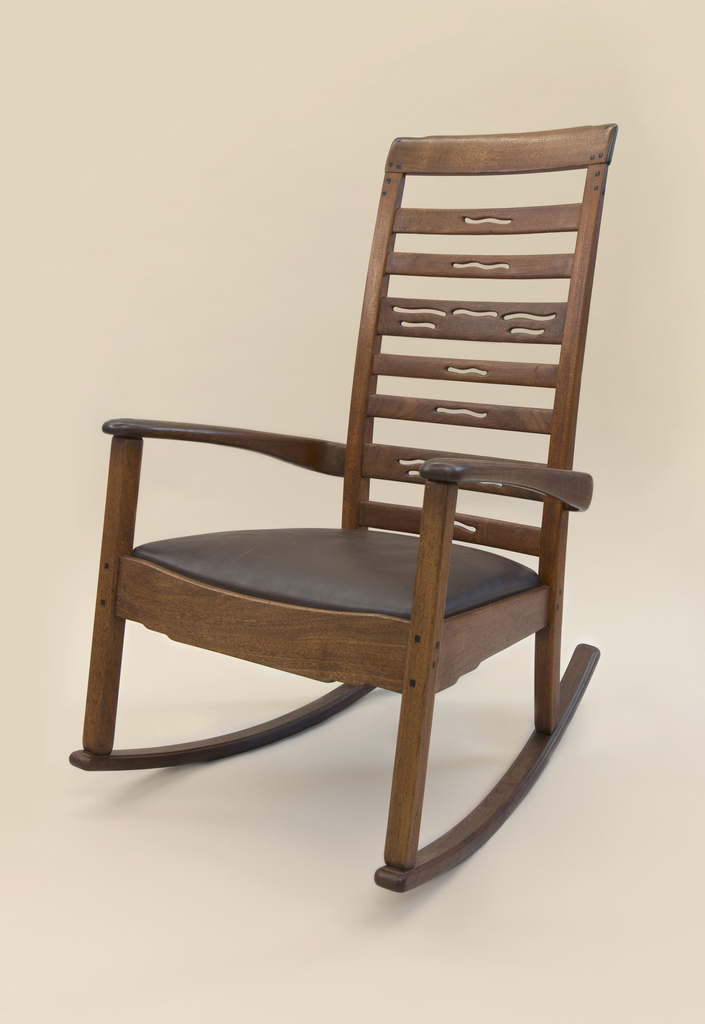 "Ladder back rocking chair with leather seat. Arms are softly rounded and apron is articulated with a ""cloud lift"" profile. Ebony pegs and splines provide a decorative focal point, upholstered seat sets into frame."
