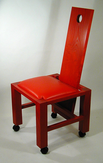 Red wooden chair with straight back panel, with hole at the top, which reaches nearly to the ground. Square seat with leather cushion framed by wood; straight legs terminating in black wheels.