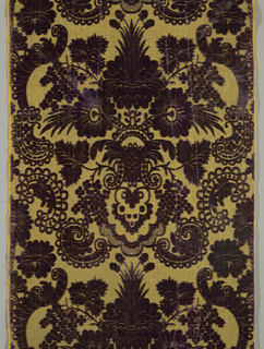 Vestment with purple cut velvet pattern of large symmetrical floral motif with leaves, incorporating large single flowers and branches of flowers on a yellow background faced with gilded metal strips.