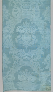 Length of blue damask has dense scrolls and flowers that create medallion shapes, enclosing alternate flower bouquets.