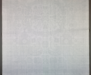 White damask napkin has a field of a horizontally and vertically symmetrical pattern comprised of a wreath of flowers with paisley or cone-like pendants hanging from each corner. Borders have a floral vine twisting around a bar, and each corner has a rosette.