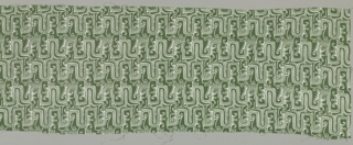 Green ground with an allover pattern of white fretwork ornamented with scrolls. This design was based on an Aztec pottery stamp dating from the pre-Columbian period in Mexico.