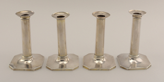 Set of four candlesticks. Square, plain bases with clipped corners to form octagon. Tubular plain shaft with molded bands at base juncture and at lip. Removable nozzles with curved plain flange. Originally gilded; traces of gilding on outer surface and fully gilded on underside. Each engraved on edge of base, in script: Al. S.