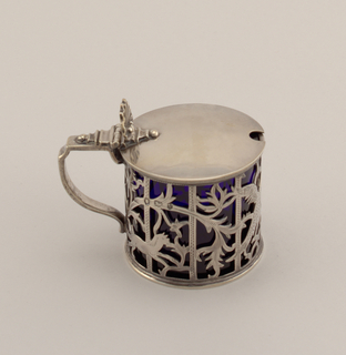 Cylindrical cage (a) with animals and birds among leafy scrolls, in cut-out silver. Strap handle, flat on top. Hinged cover with shell thumbrest, and hole for spoon. Cylindrical, dark blue glass insert (b).