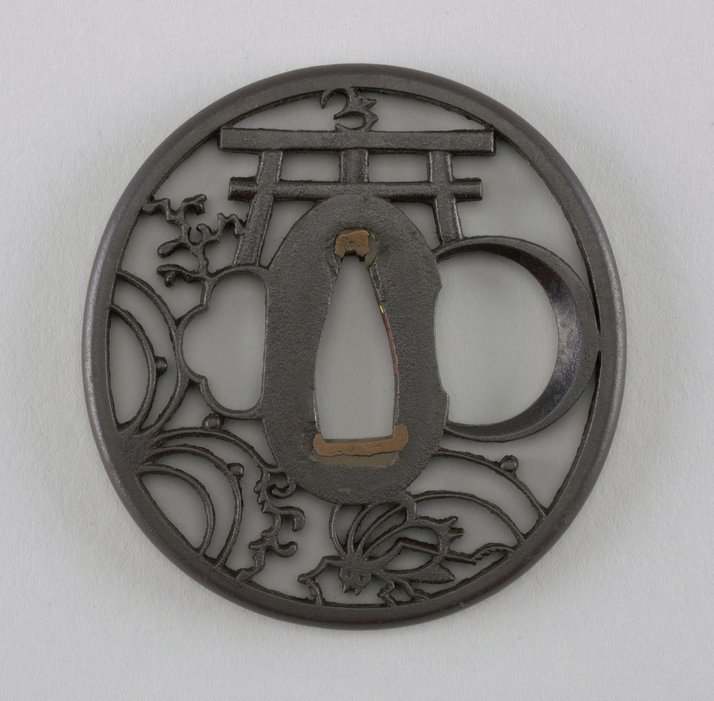Probably Akaska school of Edo. This iron tsuba is naga maru gata (round) in shape, and is crafted in the ji sukashi openwork style, with a positive design showing mika tsuki, korogi, ran and torii (crescent moon, cricket, orchid and shrine gate), possibly making an allusion to a poem. At the center is a wide nakago-ana, an opening through which the sword passes, with sekigane (plugs added to fit the tsuba to a sword) made of shakudo (a soft copper and gold alloy). Surrounding this is the seppadai, a flat oval area that has a migaki ji (smooth) surface finish. On either side are ryo-hitsu, openings for the kozuka (utility knife) and the kogai (skewer tool). At right is sashi ura, the side which faces the blade, whose opening takes the negative form of a moon. Opposite is the sashi omote side, which faces the sword hilt. Its tri-lobed opening is of the suhama type, and symbolically represents the coastline of Horai, the holy island of the Immortals. The rim of the tsuba is round, or maru-mimi.